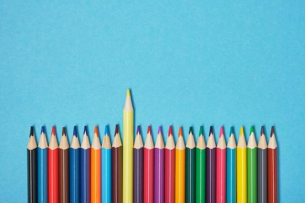 Geel potlood onderscheidt zich van andere kleurpotloden op een blauwe achtergrond kopie ruimte bovenaanzicht