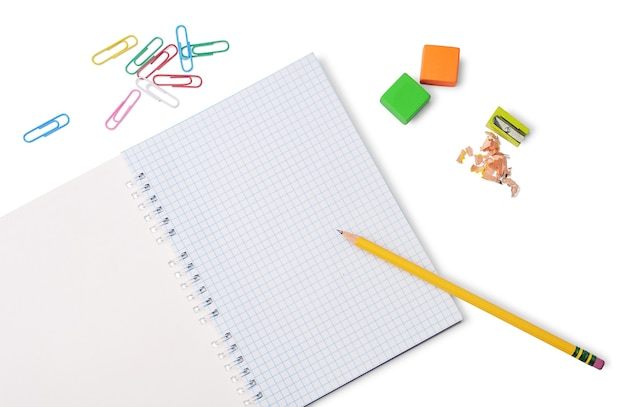 Geel potlood, raster blocnote, kleurvlakken, puntenslijper en paperclips geïsoleerd op een witte achtergrond. school- of kantoorbenodigdheden.