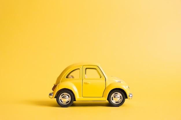 Geel. retro speelgoedauto op geel. zomer reizen concept. taxi