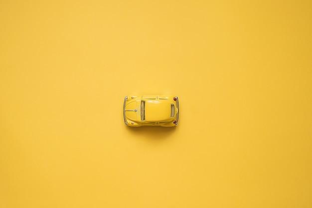 Geel. retro speelgoedauto op gele .. zomer reizen concept. taxi. bovenaanzicht.