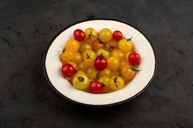 Geel rode tomaten verse rijp binnen witte plaat op een grijze vloer