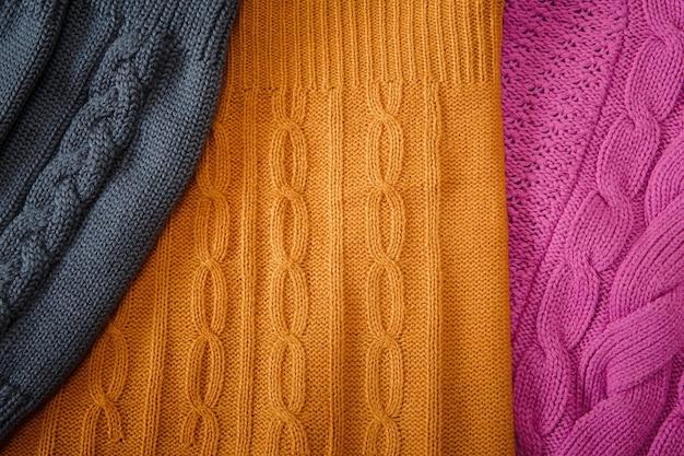 Geel roze en grijs gebreide artikelen met vlechten en patroon handgemaakte fancywork achtergrond