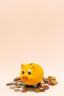 Geel spaarvarken met een stapel muntstukken