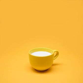 Geel stilleven van kopje melk