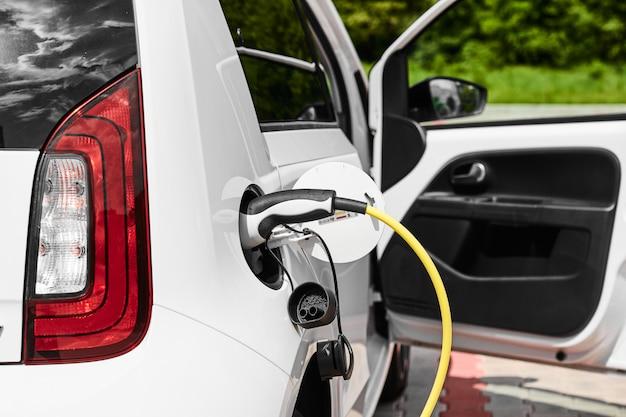 Geel stopcontact dat een elektrische auto in de straat laadt. voeding aangesloten op de elektrische auto