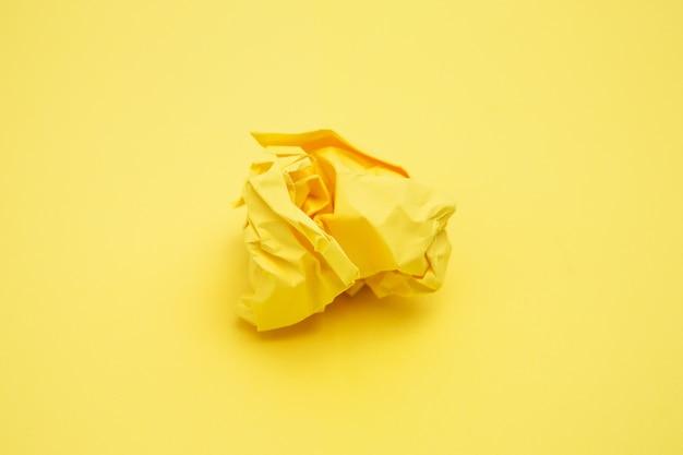 Geel stuk van verfrommeld papier op gele achtergrond