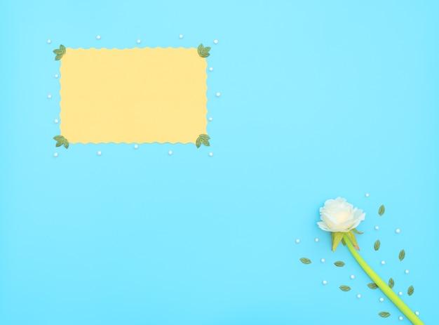 Geel vel papier en witte bloem met groene bladeren en witte kralen op blauwe achtergrond.
