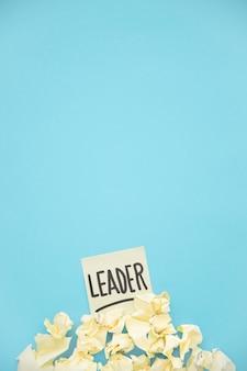 Geel verfrommeld document op leiders kleverige nota over de blauwe achtergrond