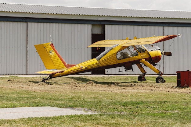 Geel vintage vliegtuig op het vliegveld