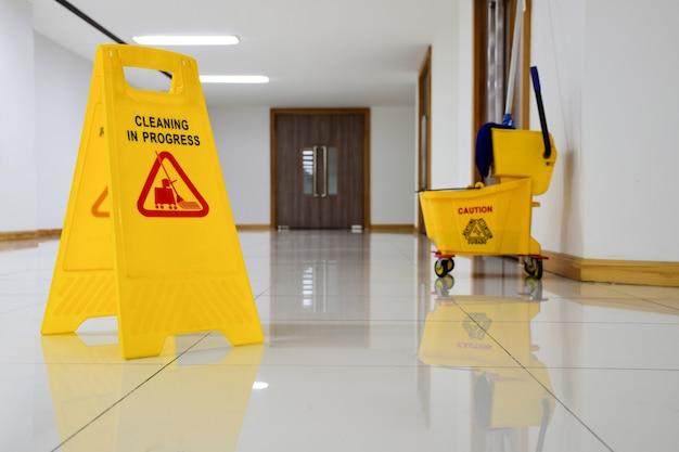 Geel waarschuwingsbord met bericht reiniging bezig en schoonmaakwagenachtergrond