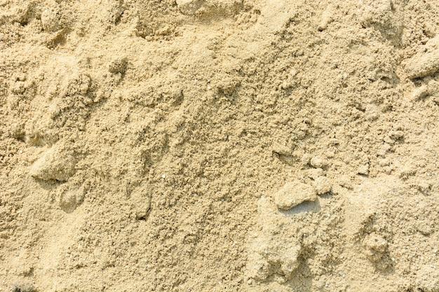 Geel zand voor de achtergrond van de bouwtextuur