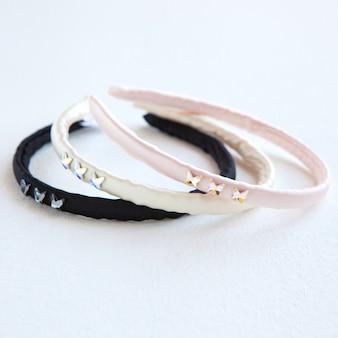 Geel zwart en roze zijden haar hoepel geïsoleerd op wit plat leggen kappersgereedschap en accessoires