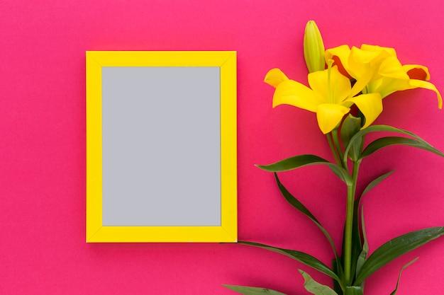 Geel zwart kader met gele leliebloem en knop op roze achtergrond