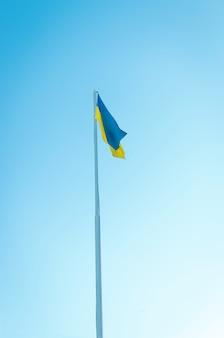 Geelblauwe vlag van oekraïne op een paal tegen de blauwe hemel