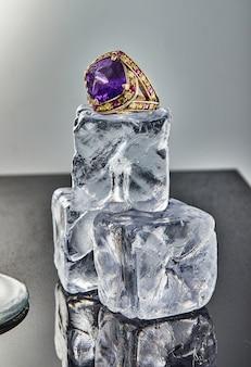 Geelgouden ring met amethist op ijsblokjes op een grijze achtergrond met reflectie. sieradenkunst en productverkoop