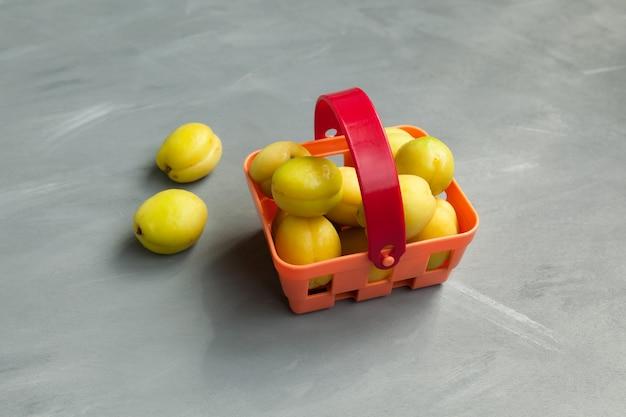 Geelgroene abrikozen in een winkelmandje. nieuwste trend - onrijp fruit eten.