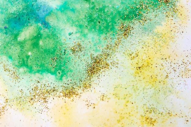 Geelgroene aquarelvlekken met glitters. abstracte achtergrond