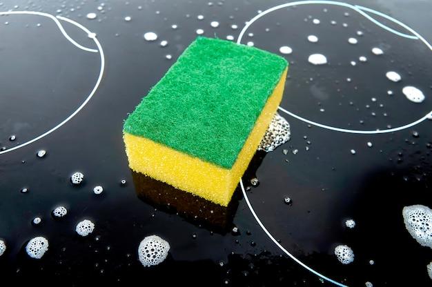 Geelgroene spons op het zwarte oppervlak van de kookplaat en afwasmiddel schuim