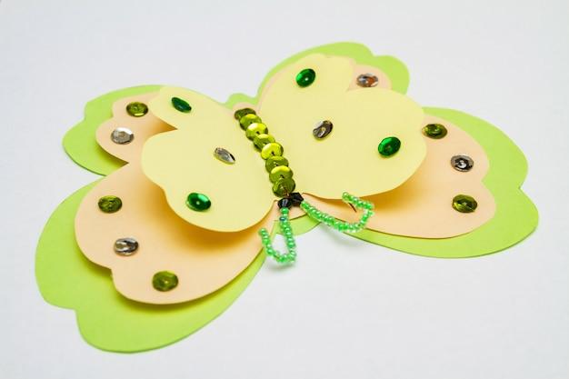 Geelgroene vlinder gemaakt van gekleurd papier, veelkleurige pailletten, paillettes en kralen