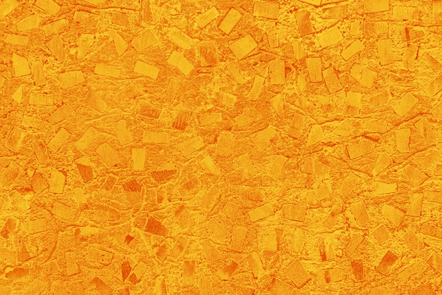 Geeloranje textuur van geschilderde muur met willekeurig mozaïekpatroon