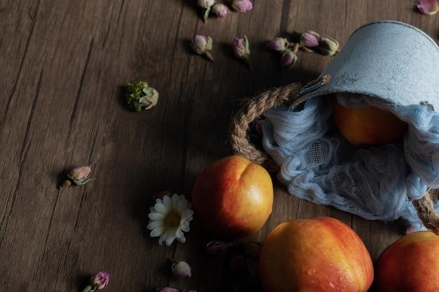 Geelrode perziken uit een blauwe metalen emmer.