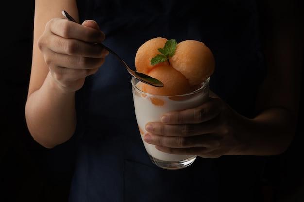 Geelvlezige meloen werd in een ronde bal geschept als ijs. zet in een helder glas gegarneerd met verse melk, zoet en heerlijk. maak een foto op een zwarte achtergrond