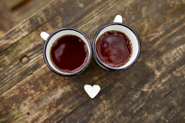 Geëmailleerde kopjes thee in de natuur op houten oppervlak met marshmallow