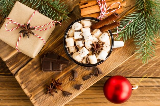 Geëmailleerde mok met chocoladedrank en marshmallow op een houten landelijke tafel met een geschenkdoos en stukjes chocolade in de buurt.