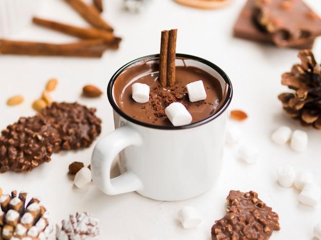 Geëmailleerde mok warme chocolademelk met kaneel en marshmallows