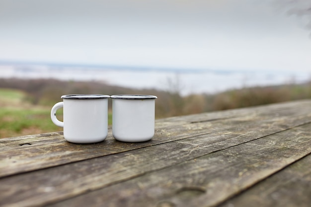 Geëmailleerde twee kopjes thee in de natuur op houten achtergrond, liefde, reisconcept, lifestyle moment in de natuur, kopieer ruimte.