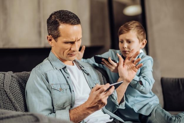 Geen aandacht. drukke jonge vader die op de bank zit naast zijn pre-tienerzoon en een spelletje speelt terwijl hij de jongen wegveegt en om aandacht vraagt