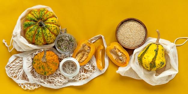 Geen afval gezond voedsel pompoen, zaden, groenten, gedroogde vruchten plat lag op oranje achtergrond. boodschappen in textielzakken, glazen potten. milieuvriendelijke, plasticvrije levensstijl met weinig afval.