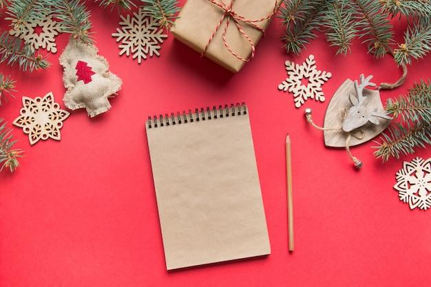 Geen afval kerstmis concept. doelen, checklist, plannen voor het nieuwe jaar. wenslijst voor nieuwjaar met houten decor op rood. bovenaanzicht plat leggen.