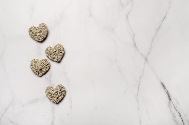 Geen afval, valentijnsdag milieuvriendelijk concept. harten met garen op witte marmeren achtergrond.