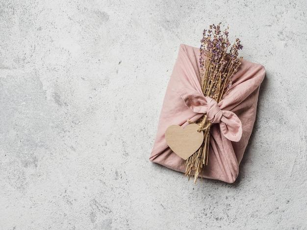 Geen afval, valentijnsdag milieuvriendelijke geschenkverpakking in furoshiki-stijl met droge lavendel en leeg ambachtelijk etiket.