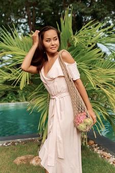 Geen afvalconcept. aziatische vrouw die eco vriendelijke mesh shopper met vers fruit.