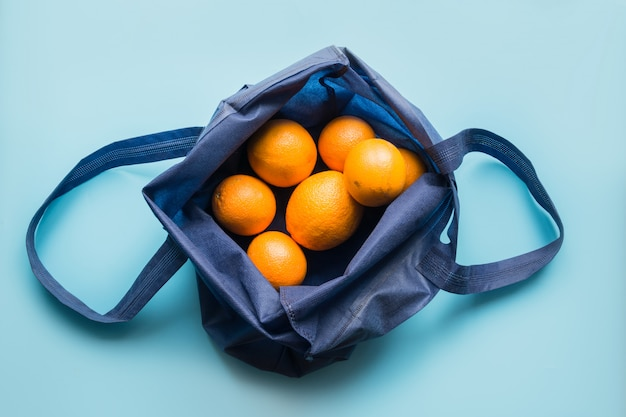 Geen afvalconcept. blauwe boodschappentas met verse sinaasappel en groenten.