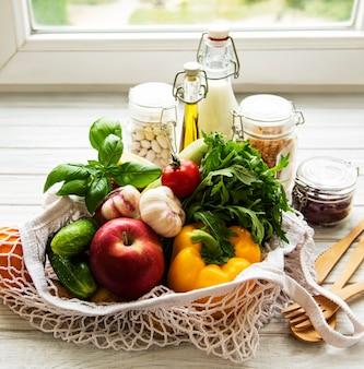 Geen afvalconcept. eco-tas met fruit en groenten, glazen potten met bonen, pasta, melk en olie. eco-vriendelijk winkel- en kookconcept, plat leggen