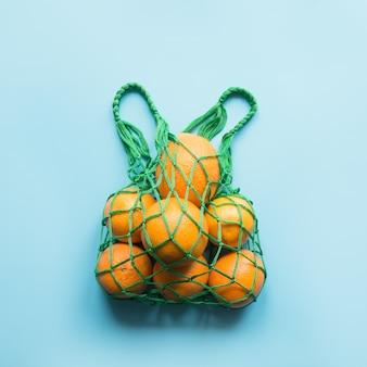 Geen afvalconcept. groene boodschappentas met sinaasappel.