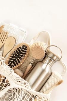 Geen afvalconcept. milieuvriendelijke accessoires - bamboe bestek, milieuvriendelijke tas, herbruikbare waterfles, haarborstel en tandenborstel. geen plastic, milieuvriendelijke levensstijl. bovenaanzicht, plat gelegd.