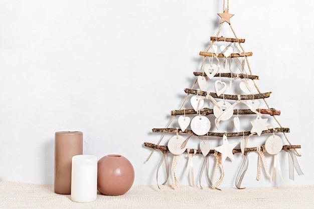 Geen afvalkerstmis met kaarsen en alternatieve handgemaakte kerstmisboom die over lichte muur hangt