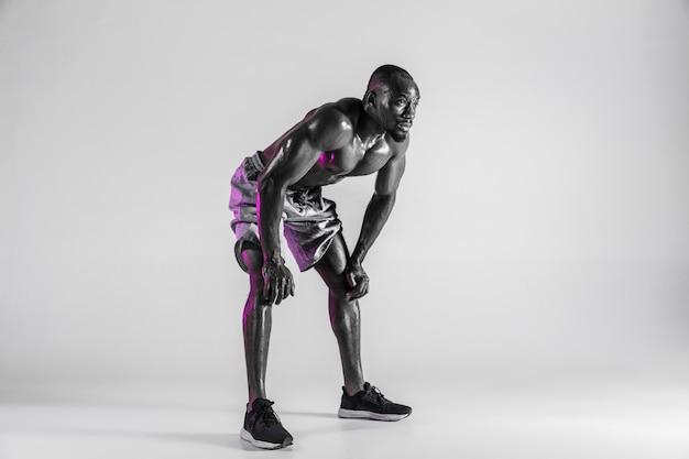 Geen angst. studio shot van jonge afro-amerikaanse bodybuilder training op grijze achtergrond. gespierd enkel mannelijk model dat zich in sportkleding bevindt. concept van sport, bodybuilding, gezonde levensstijl.