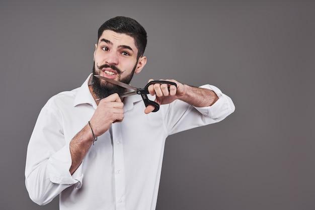 Geen baard meer. portret van knappe jonge man zijn baard knippen met een schaar en camera kijken terwijl hij tegen een grijze achtergrond staat. nieuwe trend.