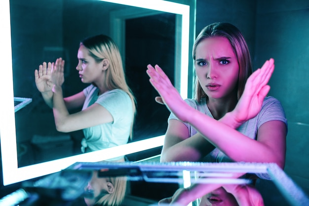 Geen drugs. handen zeggen nee. jonge mooie vrouw met gekruiste armen zegt nee tegen drugs op cocaïnelijn in het toilet van de nachtclub.