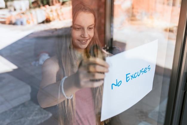 Geen excusespapier, jong meisje toont bordje door glazen raam, het nieuwe normaal