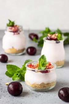 Geen gebakken cheesecake met kers in glazen potten, verse kersen en munt op een grijze steen