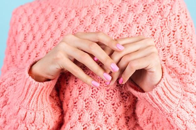 Geen gezichtsfoto van dameshanden met felroze nagelkleurmanicure op muur