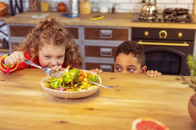 Geen honger. mooie blonde meid houdt vork in de rechterhand en kijkt naar groenten