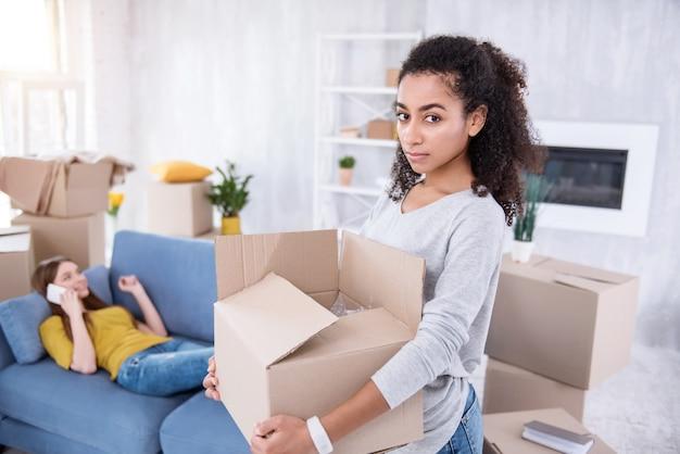 Geen hulp. mooi meisje met krullend haar met een zware doos en bezittingen uitpakken terwijl haar kamergenoot niets anders doet dan praten aan de telefoon