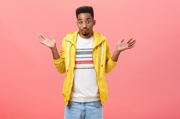 Geen idee broer. onzekere clueless afro-amerikaanse man met baard en afro-kapsel in geel trendy jasje schouderophalend met handpalmen omhoog bij schouders onzeker en onbewust over roze muur.